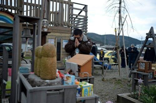 子供たちのお地蔵さんに向かい手を合わせる遠藤伸一さんと参列者(宮城県石巻市)