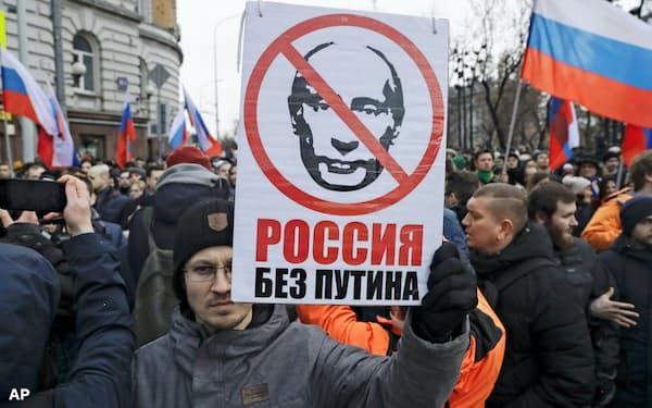 2月29日、モスクワで開かれた故ネムツォフ第1副首相の追悼行進で「プーチンのいないロシアを」と書かれたプラカートを掲げた参加者=AP
