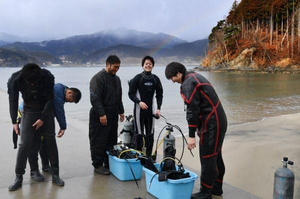 観光ダイバーが機材を準備する様子を見守る佐藤さん(右から3人目)。奥には虹がうっすらと出た(岩手県大船渡市の浪板ビーチ)