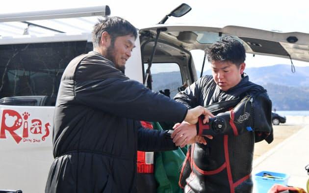 野田勇志さん(右)は高校のダイビングの授業で佐藤さんに出会った。まだ慣れないドライスーツを脱ぐのを助けられ、「早く一人でできるようになりたい」
