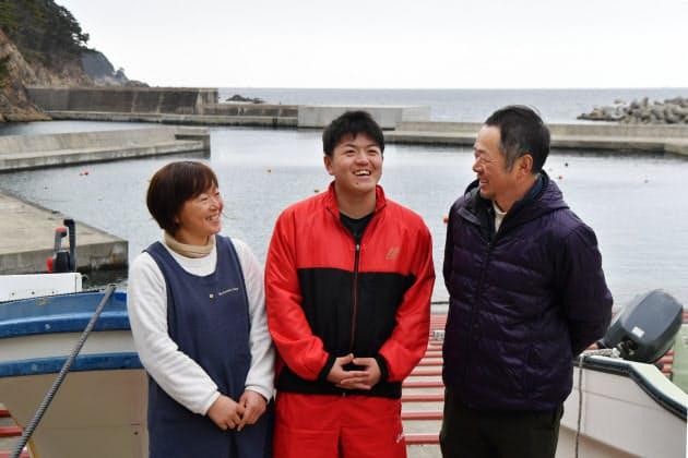父の邦広さん、母の繁美さんに囲まれ地元の吉浜漁港に立つ勇志さん(中央)。「ダイビングもいいけど、漁の方も手伝ってくれよ」と邦広さん。頼もしい笑顔を見せた(岩手県大船渡市の吉浜港)