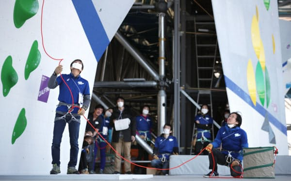 スポーツクライミングの五輪テスト大会で競技進行を確認するマスク姿のスタッフたち(3月6日、東京都江東区の青海アーバンスポーツパーク)=小幡真帆撮影