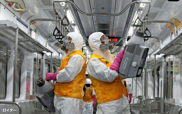韓国では公共交通機関も新型コロナウイルス対策を進める(11日、ソウルで、地下鉄の車内の消毒作業)=ロイター