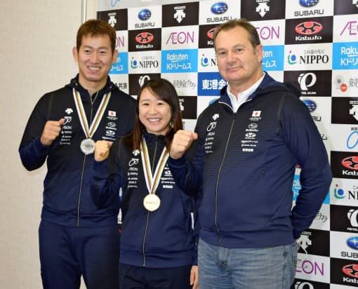 世界選手権のメダルを胸に笑顔を見せる梶原(中)と脇本(左)。右端は梶原らを指導するグリフィン・ヘッドコーチ(3日、成田空港)