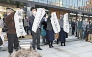 小松基地騒音訴訟の判決後、金沢地裁前で垂れ幕を掲げる原告側関係者(12日午後)=共同