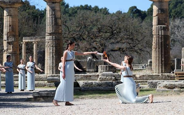 オリンピアのヘラ神殿で行われた東京五輪聖火の採火式で、聖火をつぼに移すみこ姿の女性たち(12日、ギリシャ)=代表撮影