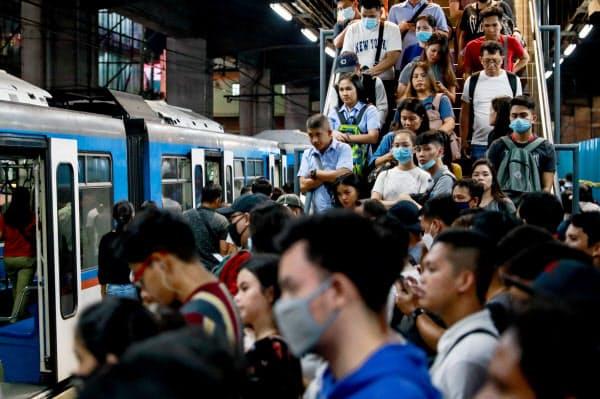 マスクをつけて電車を利用するフィリピンの人々(3月11日、マニラ)=ロイター