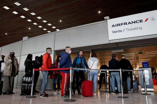 パリのシャルル・ドゴール空港には米国行きのチケットを求める人々の列ができた(12日、ロイター)