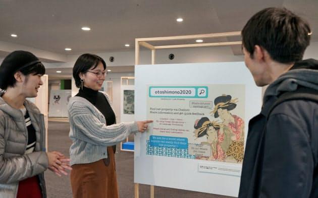 浮世絵を使ったパネルで落とし物の情報を検索できるシステムの説明をする津田塾大学の学生(記念展示会で)