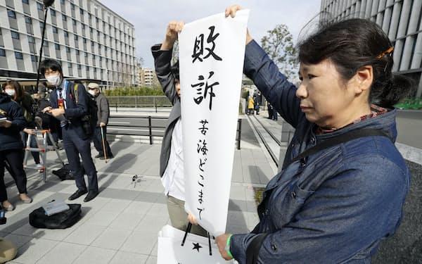 控訴審判決後、「敗訴」と書かれた垂れ幕を掲げる原告側(13日、福岡市)