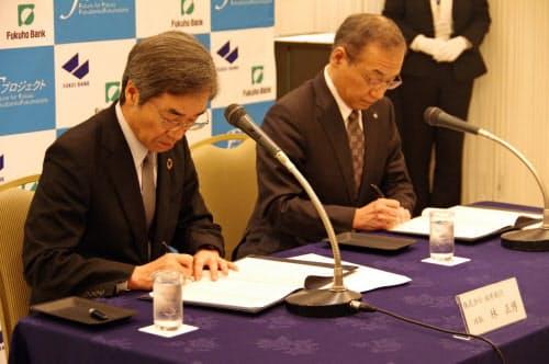 契約書に署名する福井銀の林頭取(左)と福邦銀の渡辺頭取(13日、福井市内)