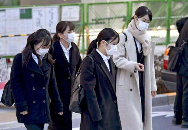 新型コロナウイルスの感染拡大を受け、マスク姿で会社説明会の会場に向かう就職活動の学生ら=1日