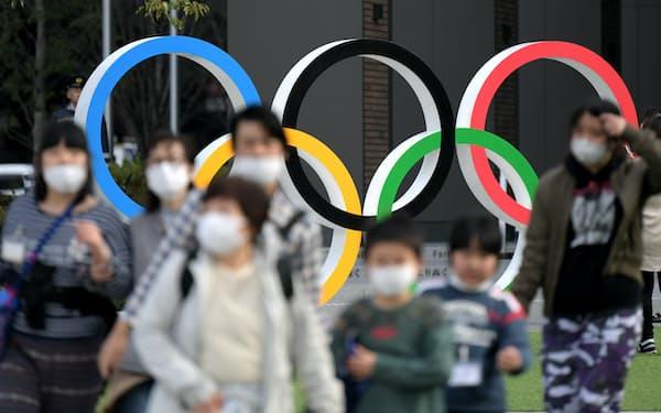 国立競技場そばに設けられた五輪マークのモニュメント。マスク姿の人が目立った(13日、東京都新宿区)