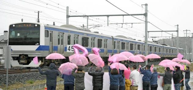 JR常磐線が全線運行再開し、富岡―夜ノ森間を走行する列車。町民らが桜をイメージしたピンクの傘などで歓迎した(14日、福島県富岡町)=共同
