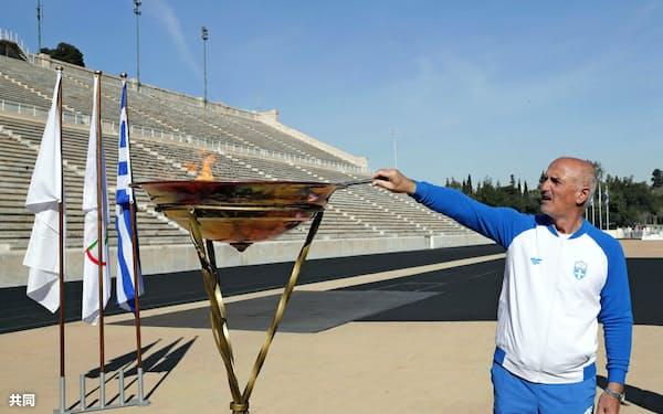アテネのパナシナイコ競技場でギリシャ・オリンピック委員会のバシリアディス聖火リレー委員長によって聖火台にともされる東京五輪の聖火(14日)=共同