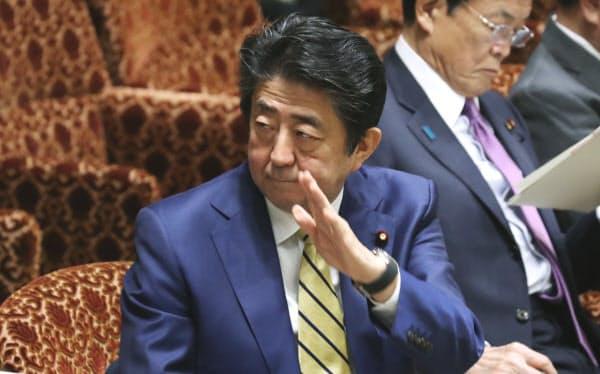 参院予算委で、新型コロナウイルスへの対応について答弁のため挙手する安倍首相(16日午前)