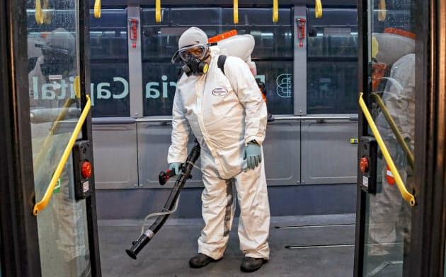 ルーマニアのブカレストでバスの車内を防護服姿で消毒する職員=AP