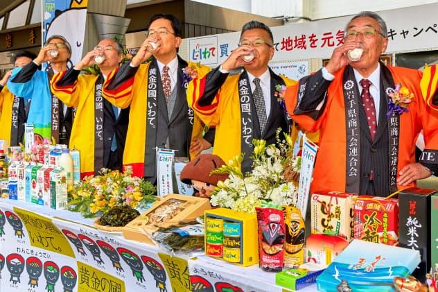 牛乳を一斉に飲むパフォーマンスで県産品の購入をアピールする達増知事(右から3人目)ら(12日、岩手県庁)