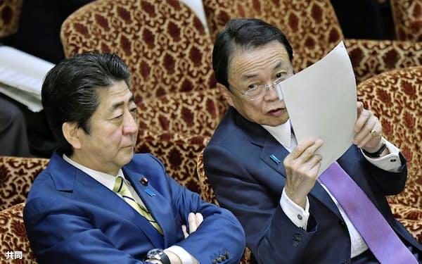 参院予算委で安倍首相(左)と言葉を交わす麻生財務相=16日午後