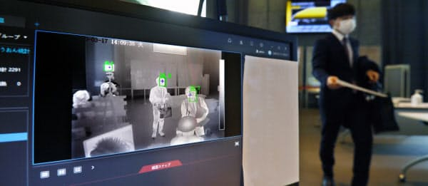 オフィスビルの受付ロビーに設置された、AIによる顔認証機能を備えた体温検知システム(3月17日、東京都千代田区)