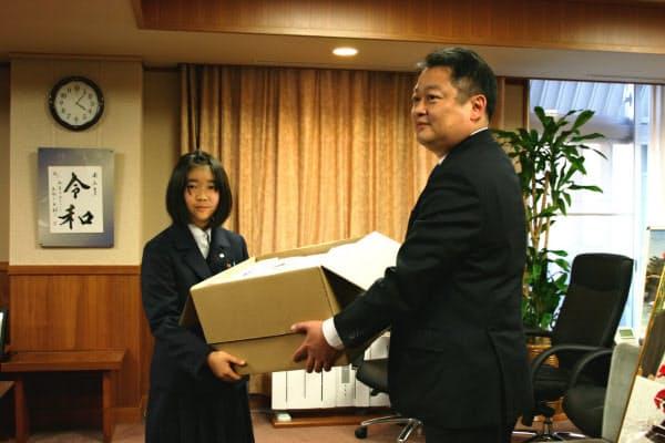 手作りマスクを長崎知事(右)に手渡す滝本さん(17日、山梨県庁)