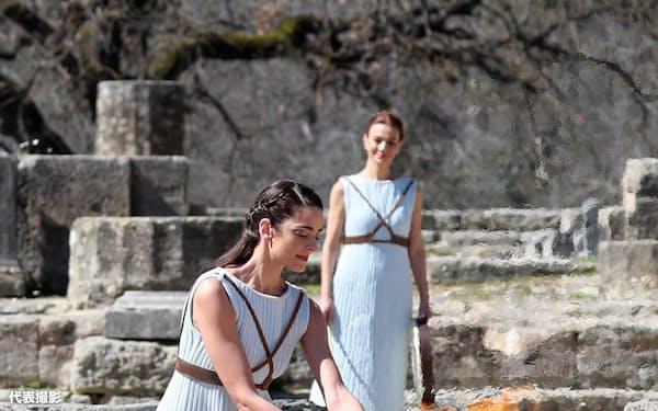 オリンピアのヘラ神殿で行われた東京五輪聖火の採火式で、聖火を採火するみこ姿の女性たち(12日、ギリシャ)