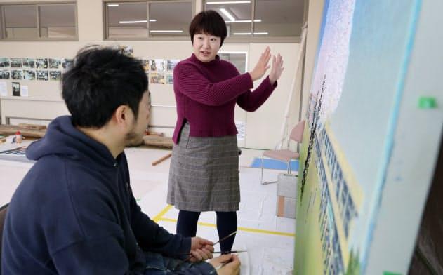 富岡町の小中学校で作品を制作している画家(左)を取材するいわき経済新聞編集長の山根麻衣子さん(福島県富岡町)