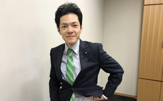 緑色のストライプ柄のネクタイとベルトを身につけます
