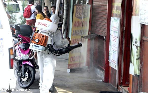 新型コロナウイルス対策で街を消毒する作業員(11日、マニラ)=AP