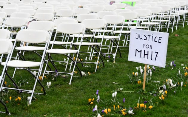 2014年のマレーシア機撃墜事件の裁判がオランダのハーグで始まるのを前に、遺族らは抗議の看板をハーグのロシア大使館の前に立てた=ロイター