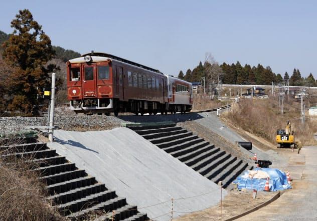 台風でレールが宙づりとなる被害が出た復旧場所を走行する試運転列車(19日、岩手県山田町)