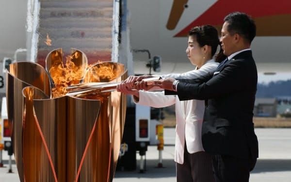 日本に到着した聖火を、聖火皿に点火する野村忠宏さん(右)と吉田沙保里さん(20日、宮城県東松島市)