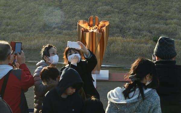 「復興の火」として展示される東京五輪の聖火の前で記念写真を撮る人たち(20日、宮城県石巻市)
