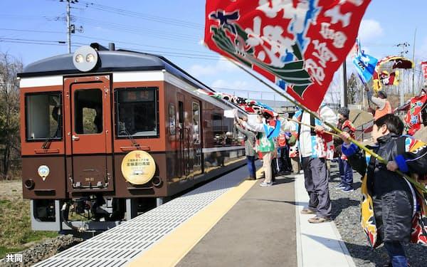 三陸鉄道リアス線の全線再開を祝い、織笠駅で記念列車に大漁旗などを振る人たち(20日午後、岩手県山田町)=共同