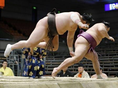 白鵬が押し出しで朝乃山(右)を下し、勢い余って土俵を飛び出す(20日、エディオンアリーナ大阪)=共同