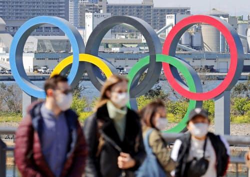 東京・お台場に設置された五輪マークのモニュメントとマスク姿の観光客(20日)=共同