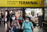 マスク姿で空港を歩く人々(18日、サンパウロ)=ロイター