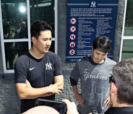 15日の練習後、報道陣の取材に応じるヤンキースの田中(左)=共同