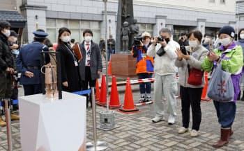 JR遠野駅前で展示された聖火を撮影する住民ら(22日、岩手県遠野市)