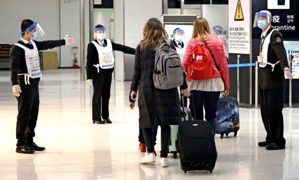 顔を覆う透明なフェースシールドとマスクを着用し、旅客(後ろ姿)を誘導する成田空港検疫所の関係者。海外から帰国した人の感染判明が増えている(21日)=共同
