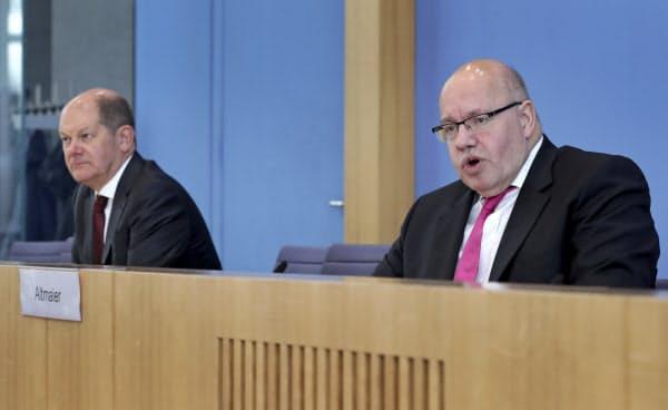 23日、ドイツの経済対策について記者会見で説明するアルトマイヤー経済相(写真右)とショルツ財務相=AP