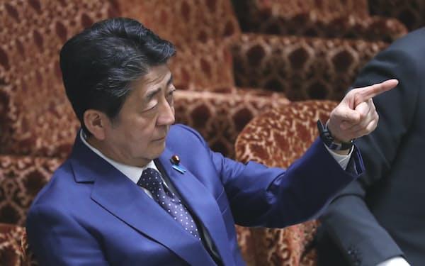 質問時間が終了した野党議員に壁のタイマーを指さす安倍首相(23日)