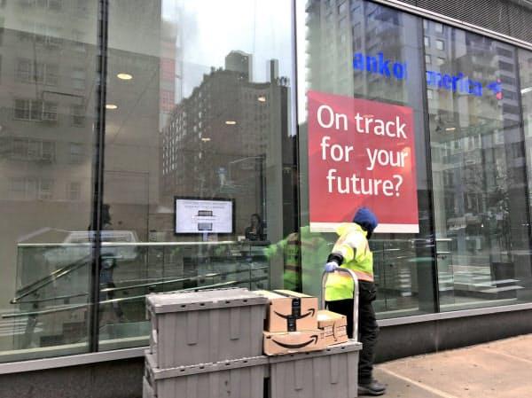 銀行は営業時間を短縮。アマゾンの荷物を運ぶ男性が通り過ぎた(23日、ニューヨーク)