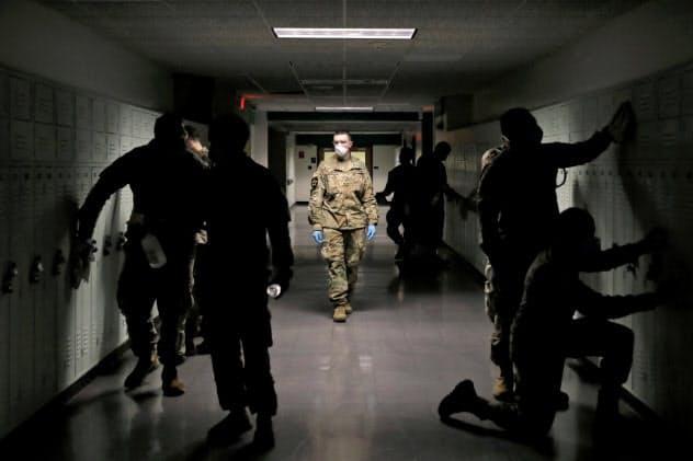 感染者の出た高校を消毒する米軍関係者ら(ニューヨーク州)=ロイター