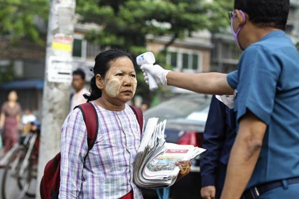 21日、ミャンマーの最大都市ヤンゴンで検温を受ける女性=AP