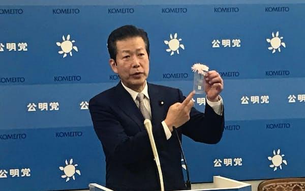 公明党の山口代表は東日本大震災の被災地で生産されたガーベラを胸に挿した(24日、国会内)