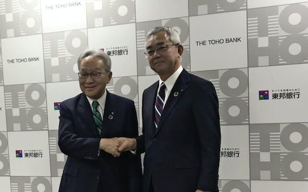 記者会見に臨む北村頭取(左)と佐藤専務