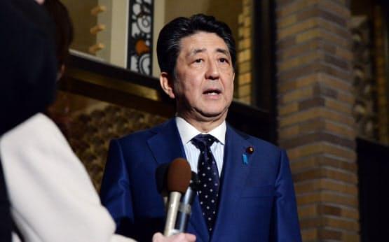 IOCのバッハ会長との電話協議を終え、記者の質問に答える安倍首相(24日、首相公邸)