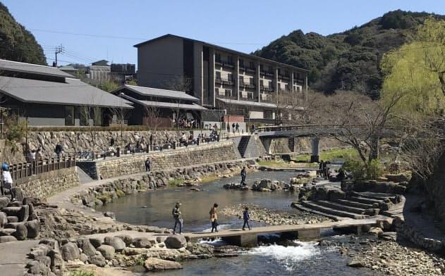 温泉街を流れる川沿いを散策する観光客