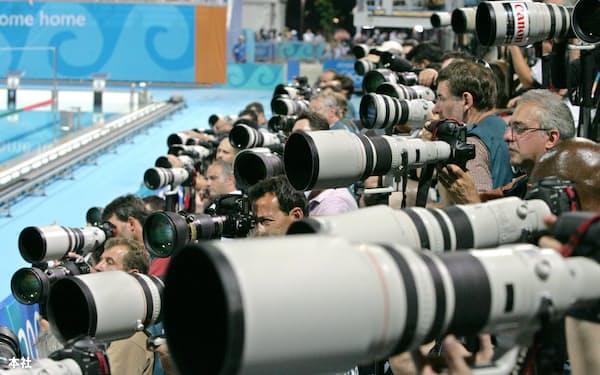 キヤノンの白い望遠レンズが目立つカメラマン席。五輪はカメラ会社にとって絶好の宣伝機会となる(2004年8月14日、アテネ五輪・競泳のカメラマン席)